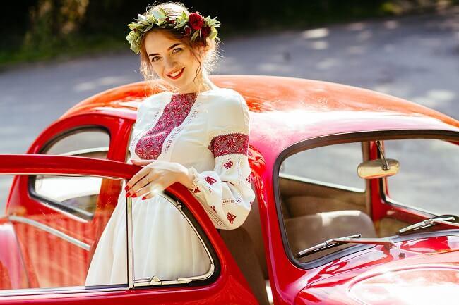 赤い車の近くに立つ女性