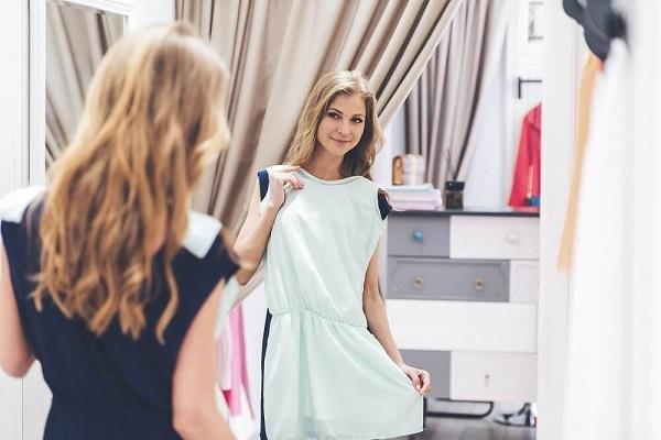 青いドレスが似合っているか鏡で確認している女性