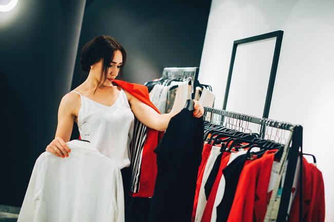 2着の服を選んでいる女性