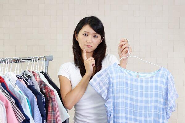 洋服選びに悩んでいる女性