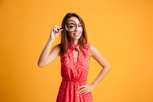 虫眼鏡でこちらを見る女性