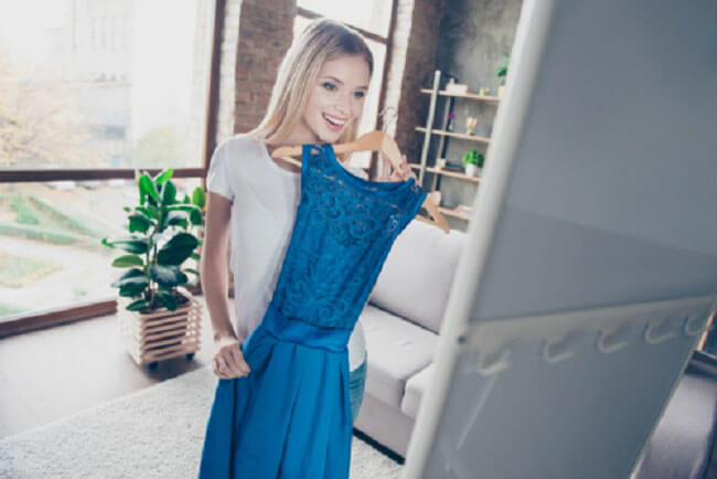 鏡の前で服を選んでいる女性